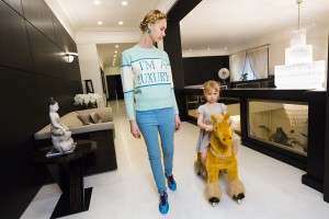 "Russian socialite and former model Ilona Stolie and her daughter Michelle, 4, in their Frank Lloyd Wright inspired mansion, located in Rublyovka, an elite residential area outside of Moscow, Russia.  Stolie wears a recreated ""I'M A LUXURY"" sweater, by fashion stylist and close friend of Stolie, Andrey Artyomov, which became a must have for all Moscow's ""it girls"" and social scene.  The unique color of the sweater Stolie wears, was created just for her.  Fashion is a very influential part of Russian wealth, and Stolie has become an icon of modern Russian style through advising bloggers and fashion editors."