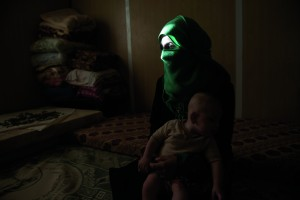 Rihab, 27, a Syrian refugee from Daraa, teaches a class on beauty to other Syrian refugees in a program run by the Norweigan Refugee Council at Zaatari camp in Jordan, August 27, 2014.    Hana Mufleh Mohammed, 16, a Syrian refugee from Daraa, poses for a portrait with her baby of 5 months at home in her trailer at the Zaatari refugee camp in Jordan, August 27, 2014.  Hana had complications with her pregnancy: she had pre-eclampsia and seizures, and spent over two weeks in the hospital unconscious after delivering. She now suffers seizures every few weeks.    While marriage under the age of eighteen is a common Syrian tradition, more and more Syrian girls are marrying at a younger age because of the insecurity of the war, and because many families feel the girls in their family may be sexually harassed if they are not under the care of a husband.  (Credit: Lynsey Addario for The New York Times)