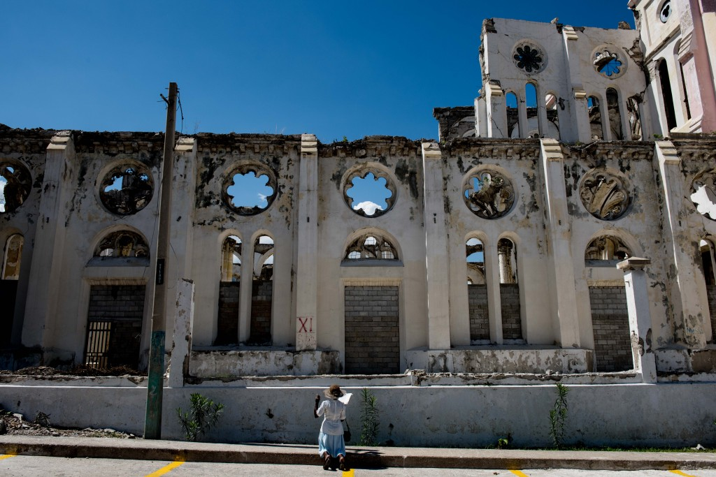 PORT-AU-PRINCE, HAITI - APRIL 3, 2015: A woman prays the stations of the cross on Good Friday outside of The Cathedral of Our Lady of The Assumption in Port-Au-Prince, Haiti on April 3, 2015. The cathedral was destroyed in the 2010 earthquake. Despite the Catholic Church shrinking in Haiti, many Haitians rely on its support.