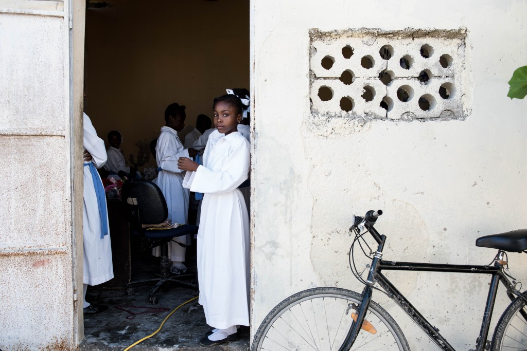 PORT-AU-PRINCE, HAITI - APRIL 5, 2015: A Catholic dancer looked out from St. AnneÕs Chapel during preparations for Easter Sunday mass in the Cite Soleil neighborhood of Port-au-Prince, Haiti on April 5, 2015. Despite the Catholic Church shrinking in Haiti, many Haitians rely on its support.
