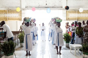 PORT-AU-PRINCE, HAITI - APRIL 5, 2015: Liturgical dancers bring the offering of the gifts during Easter mass at St. AnneÕs Chapel during Easter Sunday mass in the Cite Soleil neighborhood of Port-au-Prince, Haiti on April 5, 2015.  The gifts included various fruits and vegetables which were placed on the alter.Despite the Catholic Church shrinking in Haiti, many Haitians rely on its support.