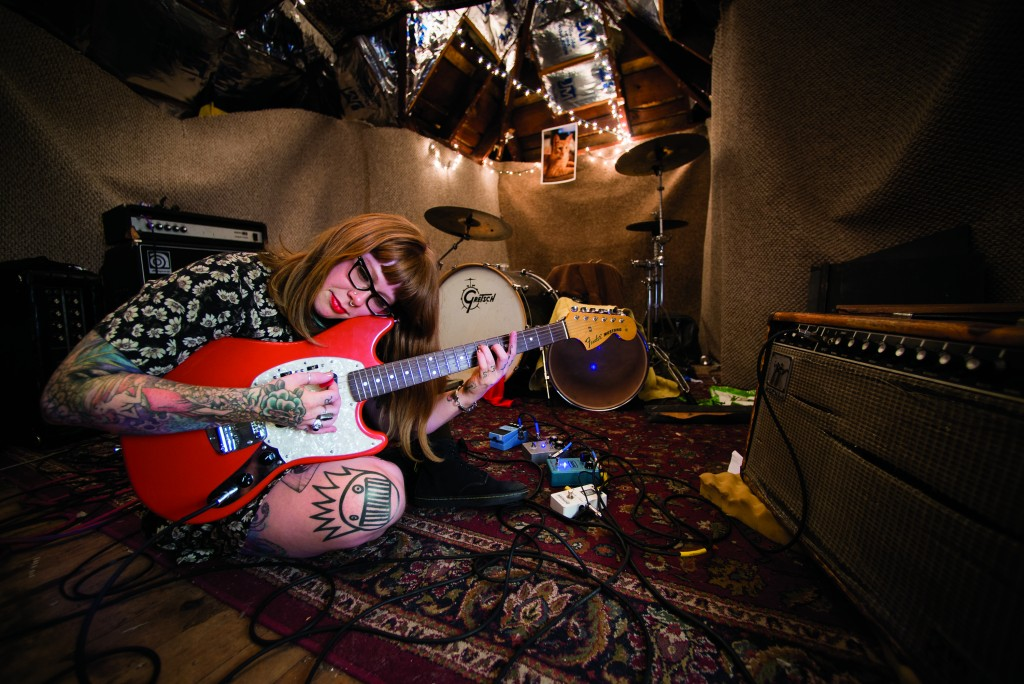 "Jesse Amesmith and her guitar ""Big Red"" in her sound studio and band practice room, in the attic of her apartment in Rochester, NY. Jesse is a guitarist and vocalist in the feminist punk group Green Dreams, with her husband Trevor Amesmith and Bass guitarist Benny ""Beyond"" Kruger. She is also a yoga instructor for Good Witch Yoga and aims to promote body positivity and mental well-being through both her practice and her music."