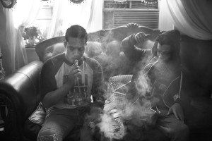 Brothers Chavier Leon (14) and Chamir Leon (25) vape in their apartment living room, 14 May 2016, Patterson Projects, South Bronx, New York.