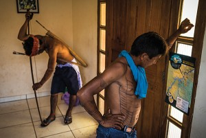 November 28, 2014. A Munduruku man looks at a map of where the San Luiz do Tapajos Dam will be built during an occupation of the FUNAI offices (Brazil's National Indian Foundation) in Itaituba, Para, Brazil. The occupation was in protest to the fact that government has refused to publish official documents that would recognize Munduruku traditional territory.