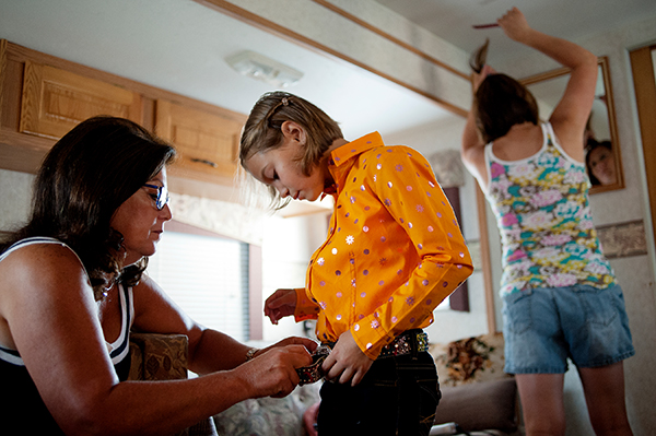 BRITTNEY LOHMILLER | blohmiller@mdn.net Helen helps Alivia Brooks adjust her belt while Angela does her hair before walking over to the showman arena at the Midland County Fair on August 17.