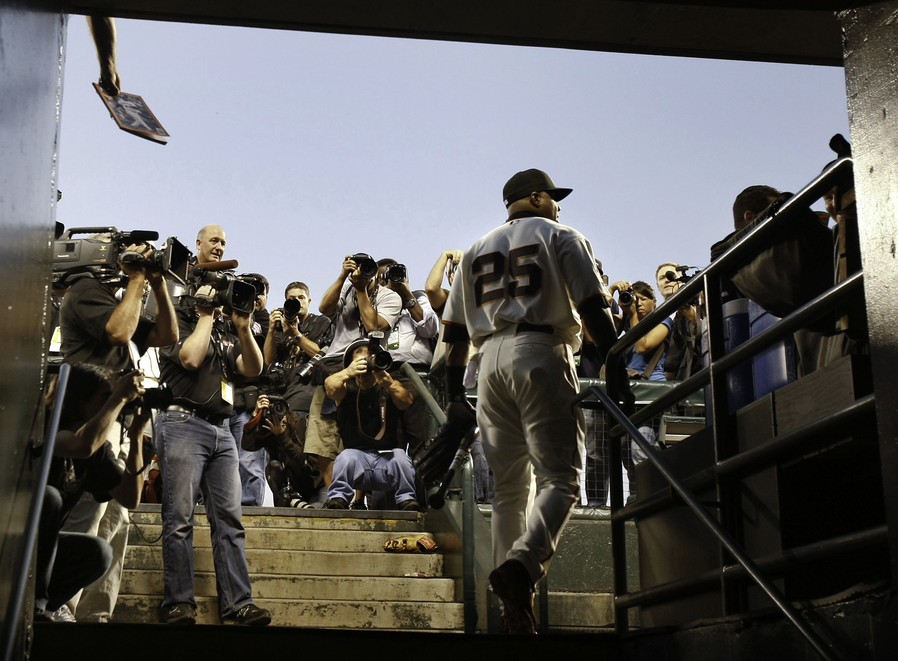 Barry Bonds approaches the dug out and passes a large crowd that has gathered during his last appearance as a major league baseball player.