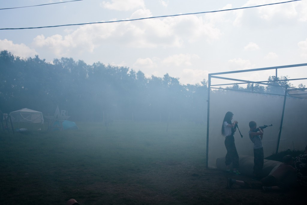 """A fake grenade is launched, setting smoke in the atmosphere as students practice a drill with air-soft guns at Военно-Исторический Лагерь Бородино 2016, the Historical-War Camp, in Borodino, Russia. 29 July 2016. They are using air-soft guns for the practice and competition. Air-soft is a sport that replicates military action, but fires non-metallic pellets. Borodino is famous for a battle fought on 7 Sep 1812 - the deadliest day of the Napoleonic Wars. 350 adolescents are in attendance, ranging in ages from 11 to 17, and lasts throughout the summer. Students learn a variety of skills from tactical training in handguns, loading and unloading automatic guns, physical endurance, knife throwing, and others. The project statement of the camp says: """"To awaken in the younger generation a keen interest in the history of the Fatherland, the glorious deeds of our ancestors, to facilitate the expansion of military-historical knowledge."""""""