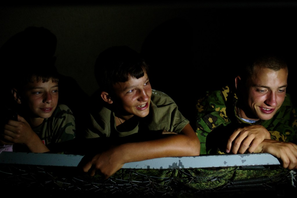 """Students from Stavropol rest in their tent before sleeping at camp. Without electricity, the students use their phones and flaslights to play games. """"Orthodox Warrior"""" camp takes place in Diveevo, the center of pilgrimage for Orthodox Christians in Russia, 3 August 2016. The relics of one of the most revered saints, St. Seraphim, are celebrated on the 1 of August, attracting pilgrims from all across the country. The participants of the camp train not only in martial arts and tactical training, but unite under their Orthodox faith. Various competitions are held throughout the week, including Cossack dagger training and military tactical training. Attendees come from all across Russia, including regions like Stavropol and Saint Petersburg."""